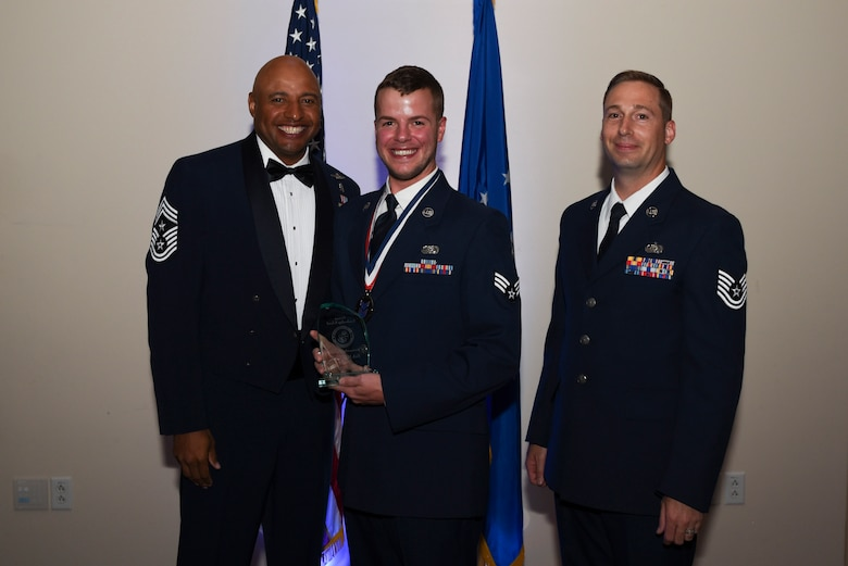 Senior Airman Matthew C. Bruce, 460th Space Communication Squadron client system technician, receives the Distinguished Graduate Award during Airman Leadership School Class 17E graduation June 22, 2017, on Buckley Air Force Base, Colo.  The Distinguished Graduate Award is awarded based on peer-leadership points and instructor evaluations.  (U.S. Air Force photo by Airman 1st Class Holden S. Faul/ released)