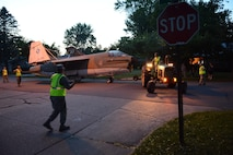 Members of the 115th Fighter Wing Crash, Disaster or Disabled Aircraft Recovery Team in coordination with Wausau city officials, police and city workers move a 1969 A-7 Corsair II aircraft through the streets of Wausau behind a 1966 John Deere 4020 tractor June 13, 2017 in Wausau, Wis.