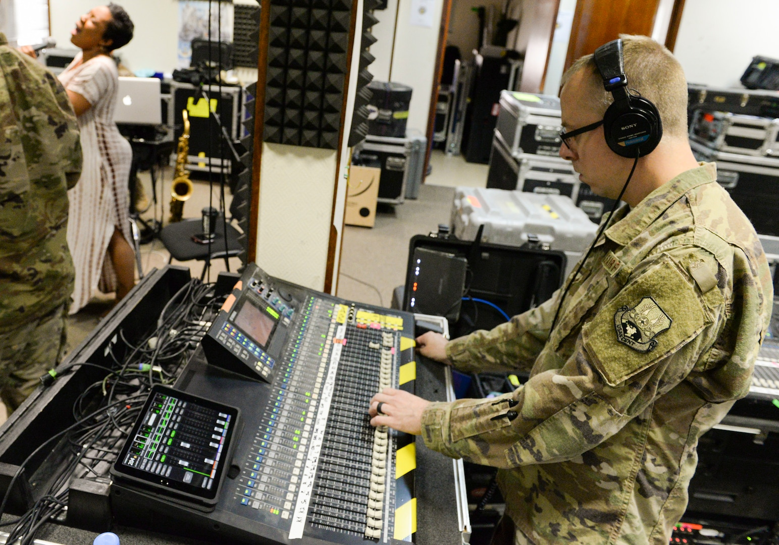 U.S. Air Force Airman 1st Class Daniel McCoy, audio engineer assigned to the Air Force Central Command Band, adjusts the sound board during a band practice held in preparation for a concert with Melinda Doolittle, background left, at Al Udeid, Air Force Base, Qatar, May 25, 2017. The AFCENT Band, stationed at Al Udeid, travels throughout the Central Command Area of Responsibility in support of building partnerships, boosting morale, and providing diplomacy and outreach to host nation communities. (U.S. Air Force photo by Tech. Sgt. Bradly A. Schneider/Released)