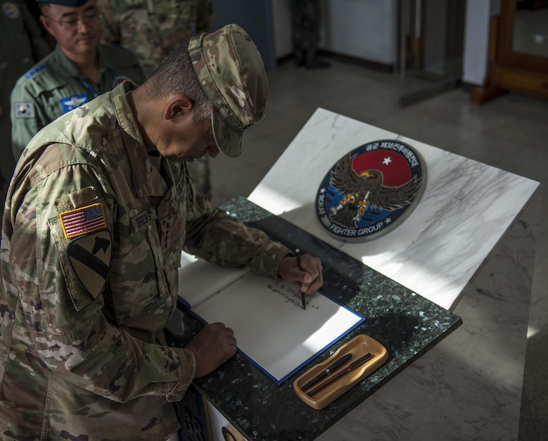U.S. Army Gen. Vincent K. Brooks, U.S. Forces Korea commander, signs a guest book June 22, 2017, during a visit at Kunsan Air Base, Republic of Korea. Brooks visited Kunsan Air Base to discuss the operational and support capabilities the different squadrons provide to the USFK mission and familiarize himself with the base. (U.S. Air Force photo by Senior Airman Colville McFee/Released)
