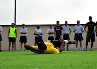 """U.S. Air Force Airman 1st Class Derrick Norman, 51st Force Support Squadron fitness specialist, instructs members of Osan Air Base on how to do oblique crunches during the """"Rogers Fit Workout"""" challenge June 23, 2017 at Osan AB, Republic of Korea. The 731st AMS along with the Osan Top Three Heritage Committee and the 51st Force Support Squadron Fitness Staff unveiled a memorial and hosted the """"Rogers Fit Workout"""" challenge in honor of Rogers, who has passed away May 20, 2016, due to injuries she sustained from helping a family escape a burning apartment building. (U.S. Air Force photo by Senior Airman Franklin R. Ramos/Released)"""