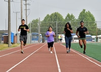 """Members of Osan Air Base run on the track during the """"Rogers Fit Workout"""" challenge June 23, 2017 at Osan AB, Republic of Korea. The 731st AMS along with the Osan Top Three Heritage Committee and the 51st Force Support Squadron Fitness Staff unveiled a memorial and hosted the """"Rogers Fit Workout"""" challenge in honor of Rogers, who has passed away May 20, 2016, due to injuries she sustained from helping a family escape a burning apartment building. (U.S. Air Force photo by Senior Airman Franklin R. Ramos/Released)"""