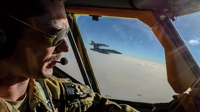 Captain Timothy Black pilots KC-135 Stratotanker on combat refueling mission over Southwest Asia while two Navy F/A-18C Hornets fly alongside, May 21, 2017 (Air National Guard/Andrew J. Moseley)
