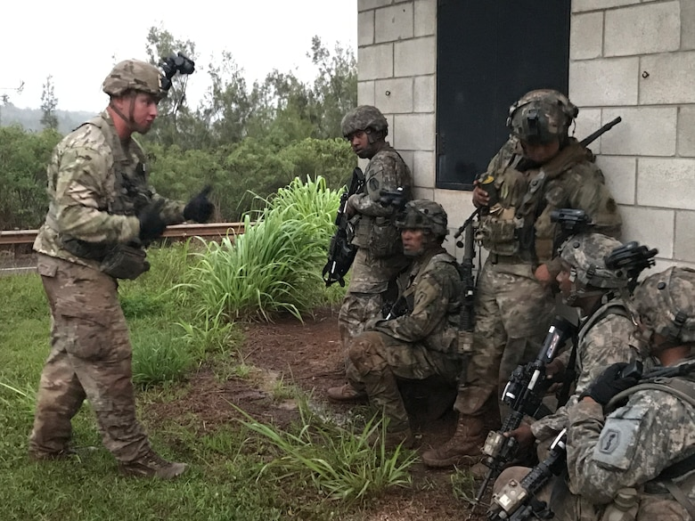 Army Reserve Soldiers of Echo Company, 100th Battalion, 442nd Infantry Regiment receive instruction from an Observer/Controller (OC) of the 196th Infantry Brigade (Training Support Brigade) during exercise Lava Forge, at Kahuku Training Area, Hawaii.
