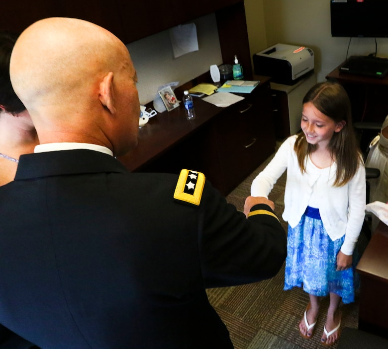 Lt. Gen. Charles D. Luckey, Chief of Army Reserve and Commanding General, United States Army Reserve, thanks Haley McMahon, Maj. Gen. David Conboy's granddaughter, with a fist bump for a drawing she gave him prior to Conboy's retirement ceremony at Fort Bragg, NC, June 23, 2017. The  CG stated that Conboy was instrumental in providing him with a candid and complete view of where the Army Reserve currently is and where it needs to go. (U.S. Army photo by Staff Sgt. Felix R. Fimbres)
