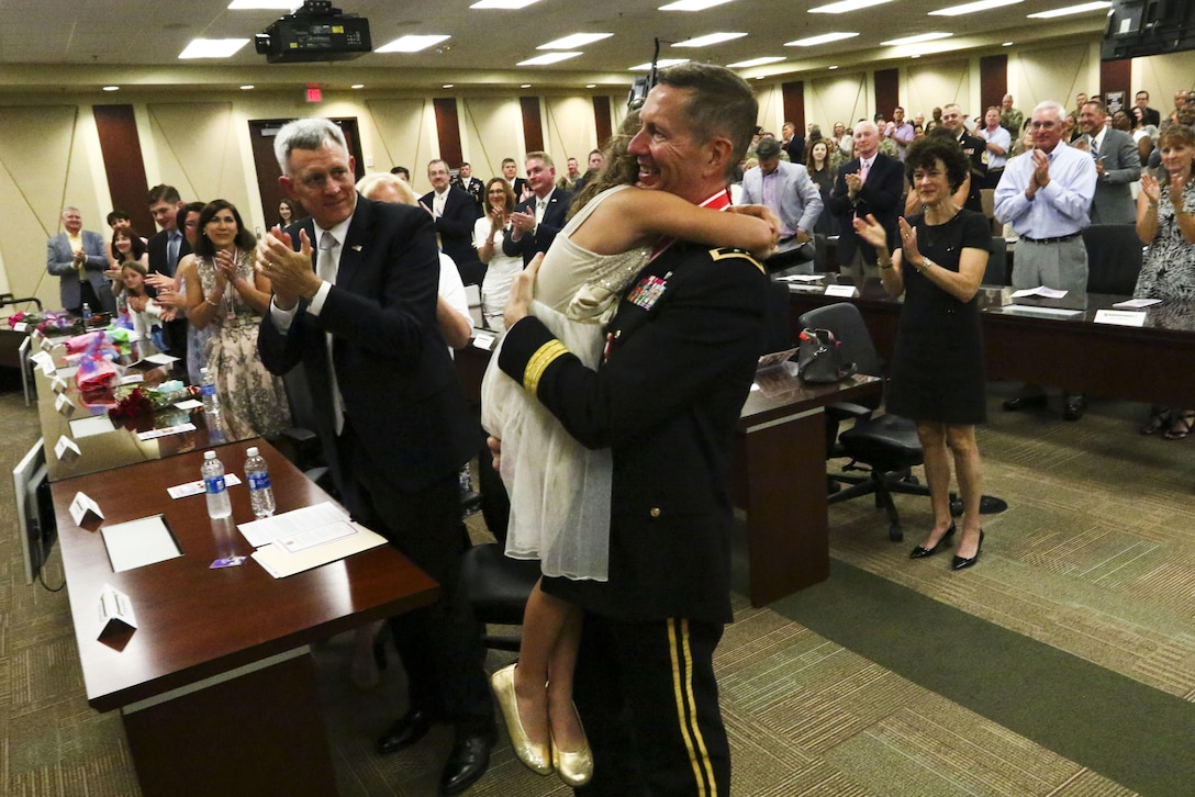 Maj. Gen. David Conboy, U.S. Army Reserve Command Deputy Commanding General, Operations, hugs his daughter after her performance during his retirement ceremony at Fort Bragg, NC, June 23, 2017. The ceremony honored Conboy for his impact on not only the U.S. Army Reserve, but the nation and its allies as well. (U.S. Army photo by Staff Sgt. Felix R. Fimbres)