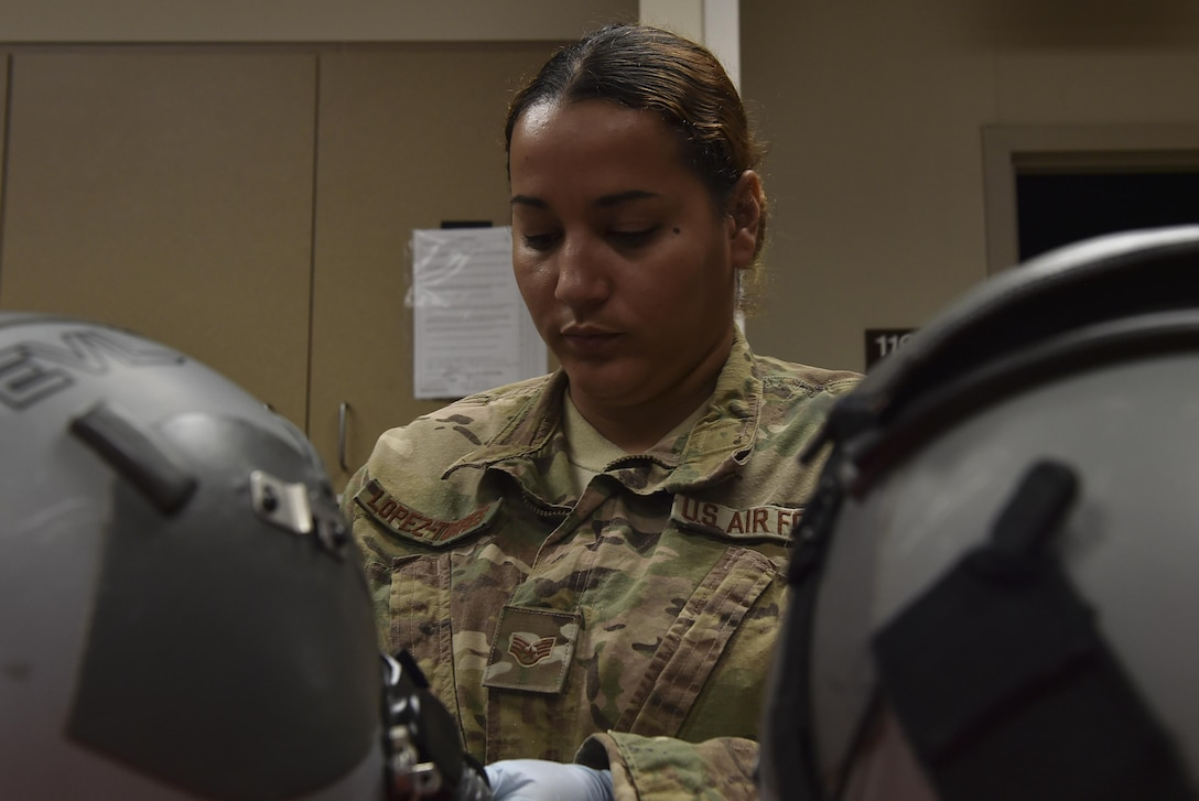 Staff Sgt. Carmen Lopez-Torres, an aircrew flight equipment technician with the 1st Special Operations Support Squadron, performs a 30-day visual inspection on aircrew helmets at Hurlburt Field, Fla., June 15, 2017. The 30-day visual inspection requires that AFE technicians examine the helmet and mask for any damage or missing components. (U.S. Air Force photo by Airman 1st Class Rachel Yates)