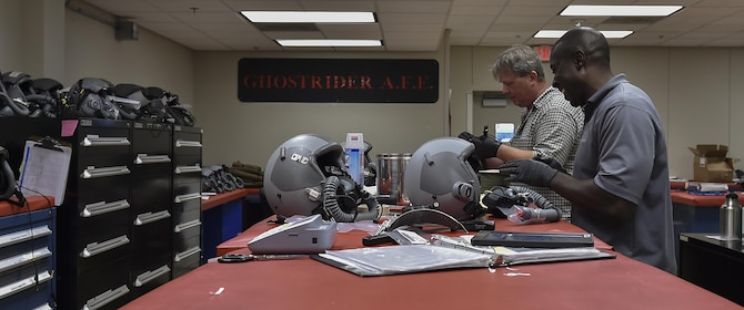 Ephraim Thomas, right, and James Vanherwaarden, aircrew flight equipment technicians with the 1st Special Operations Support Squadron, perform 30-day visual inspections on aircrew helmets at Hurlburt Field, Fla., June 15, 2017. The helmets are inspected for damages and disinfected every 30 days, while the helmets are completely broken down and rebuilt every 90 days. (U.S. Air Force photo by Airman 1st Class Rachel Yates)