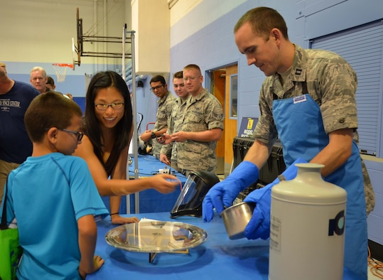 """Capt. Barron Stone, a scientist with the Air Force Technical Applications Center, and his wife, Olivia, also a scientist, demonstrate quantum levitation to a young man attending the 45th Space Wing's """"All SySTEMs Go"""" event June 17, 2017.  Stone is seen using liquid nitrogen to cool a non-magnetic disk to cause it to hover over the Plexiglas plate.  (U.S. Air Force photo by Susan A. Romano)"""