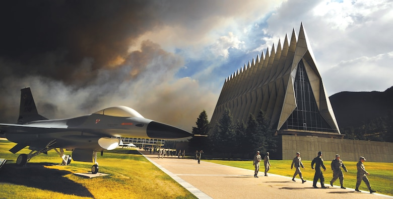 An ominous cloud of smoke from the Waldo Canyon Fire rises from the south behind the Air Force Academy's Cadet Chapel as cadets head for a briefing on evacuation procedures June 27, 2012. The Academy evacuated more than 600 families and 110 dormitory residents from the base the evening of June 27. (U.S. Air Force photo/Carol Lawrence)