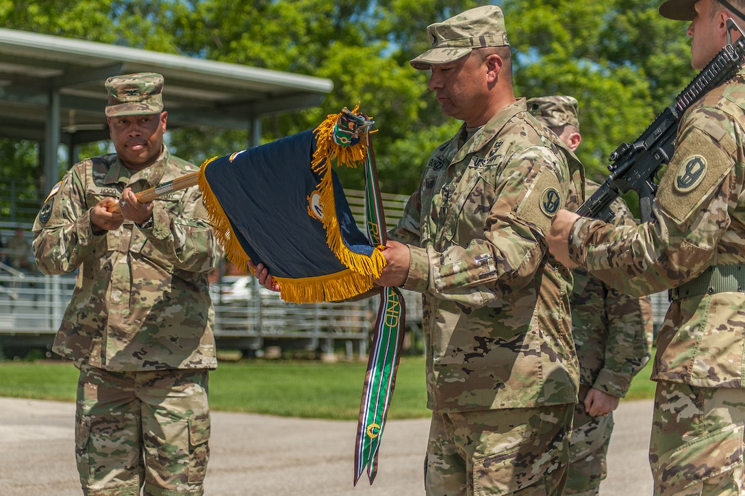 Col. Daryl Hood, 3rd Chemical Brigade commander, left, holds the guidon while Command Sgt. Maj. Jerry Gonzales unfurls the colors for the 2nd Battalion, 48th Infantry Regiment during the battalion activation ceremony Friday. The battalion was activated to support an increase to the installation's Basic Combat Training mission.   (Photo Credit: Mr. Stephen Standifird (Leonard Wood)