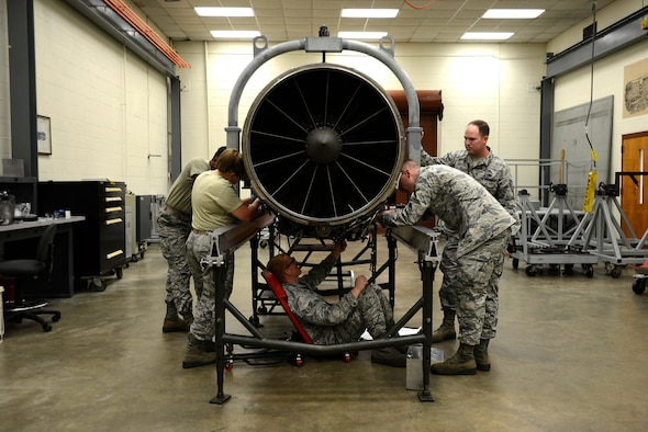 A team of four U.S. Airmen, overseen by their instructor, work together to remove the accessory drive gearbox from an F-16CM Fighting Falcon engine during training at the 372nd Training Squadron, Detachment 202 F-16 Field Training Detachment (FTD) at Shaw Air Force Base, S.C., April 25, 2017. The FTD is responsible for training not only active duty maintenance Airmen, but also Air National Guard and Air Force Reserve Airmen, and those preparing for a permanent change of station to the Pacific Air Forces area of responsibility. (U.S. Air Force photo by Senior Airman Kelsey Tucker)