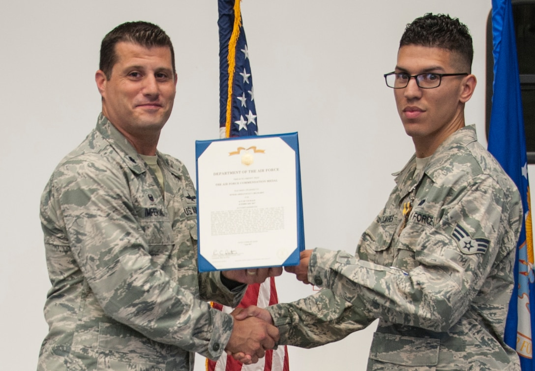 Lt. Col. Matthew Imperial (right), 96th Communication Squadron commander, presents Senior Airman Kyle Belmares, 96th CS cable and antenna systems, with an Air Force Commendation Medal at an awards ceremony June 20 on Eglin Air Force Base, Fla. Belmares was one of two Airmen recognized for life-saving care in response to a severe vehicle accident in February. (U.S. Air Force photo/Jasmine Porterfield)