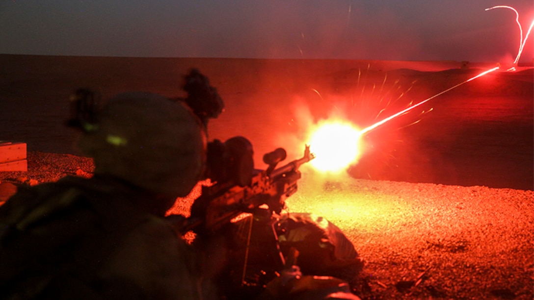 this image shows a marine firing a tracer round from a machine gun at night