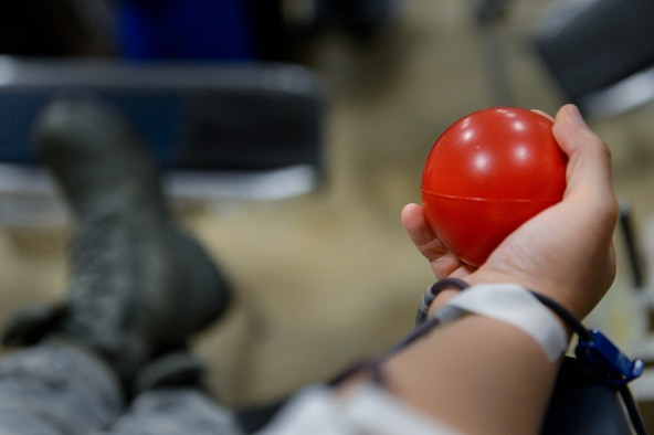 An Airman squeezes a stress ball as he donates blood at the 2017 LifeShare Blood Drive at Barksdale Air Force Base, La., June 16, 2017. Approximately every two seconds someone in the U.S. needs blood.(U.S. Air Force Photo/Airman 1st Class Sydney Bennett)