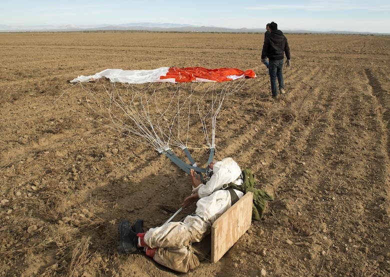 A dummy attached to a GR7000 parachute is recovered following a test drop at the ROWE drop zone south of Edwards Air Force Base. Members of the 418th Flight Test Squadron are testing a new parachute canopy for the Advanced Concept Ejection Seat II, or ACES II. (U.S. Air Force photo by Ethan Wagner)