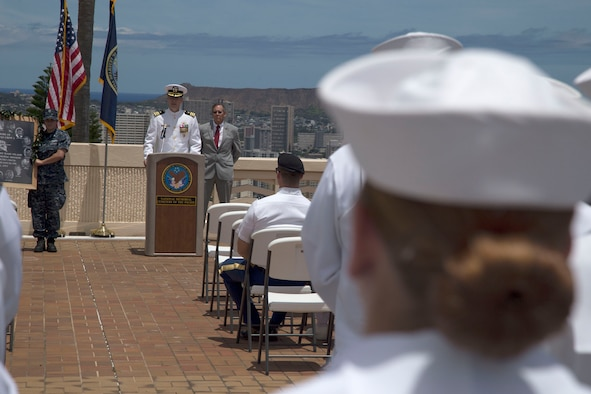 Commander Adam Hancock, Operations Officer of Strategic Communications Wing ONE and former VQ-3 Commanding Officer, salutes the ensign during a flag folding at the Crew 4 memorial ceremony in Honolulu. (U.S. Navy photo by Petty Officer 1st Class Cody R. Boyd)
