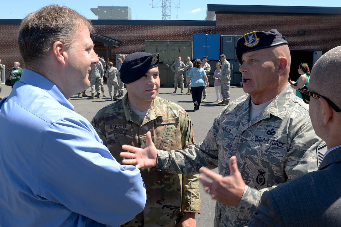 Master Sgt. Timothy J. Hackett, the traditional operations superintendent of the 157th Security Forces Squadron, and his son, Senior Airman Travis J. Hackett, of the 91st Missile Security Forces Squadron, speak with N.H. Gov. Chris T. Sununu at a deployment ceremony June 25, 2017, at Pease Air National Guard Base, N.H. Hackett is scheduled to deploy midsummer in support of Operation Freedom's Sentinel.