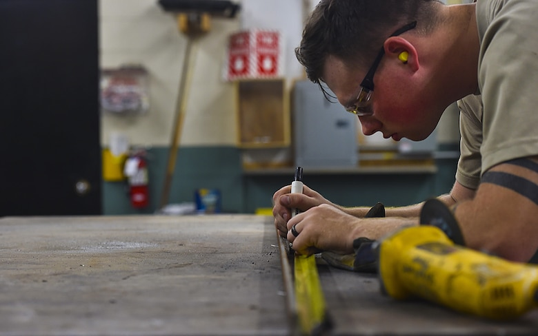 Airman 1st Class Wayne Lee, 628th Civil Engineer Squadron structural apprentice, measures an angle iron for a table leg at Joint Base Charleston, S.C., June 23, 2017. The 628th CES structures shop helps maintain structures, such as buildings and other government property, across the Air Base and Weapons Station.