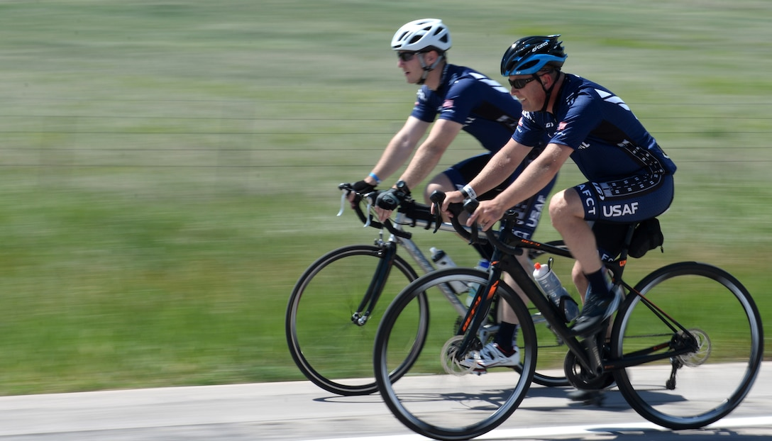 Maj. Anthony Bares, the director of wing inspections assigned to the 28th Bomb Wing Inspector General office, front, and Capt. Eben Engler, a B-1 bomber weapon systems officer assigned to the 34th Bomb Squadron, back, cycle toward Caputa, S.D., during the Ride Across South Dakota, June 4, 2017. The ride was one of two local events members of the Dakota Regional Air Force Cycling Team participated in as preparation for the Register's Annual Great Bicycle Ride Across Iowa July 23-29. (U.S. Air Force photo by Airman 1st Class Thomas Karol)