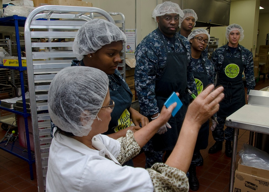 170623-N-YM720-047 PORTLAND, Ore. (June 23, 2017) - Sailors from the submarine tender USS Frank Cable (AS 40) receive instructions from an employee at Meals on Wheels resource center in Portland, June 23.  The Sailors volunteered in the kitchen to help prepare food, package the meals, clean dishes and other various tasks.  Frank Cable is in Portland, Ore. for a scheduled dry-dock phase maintenance availability. (U.S. Navy photo by Mass Communication Specialist 2nd Class Allen Michael McNair/Released)