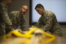 U.S. Air Force Master Sergeant John Comeens, left, 52nd Operations Support Squadron first sergeant, learns how to pack a pilot parachute during the commander's parachute shop familiarization tour at Spangdahlem Air Base, Germany, June 23, 2017. The tour gave the new squadron commander and first sergeant a chance to see the aircrew flight equipment section and experience multiple mock parachute packs. (U.S. Air Force photo by Senior Airman Preston Cherry)