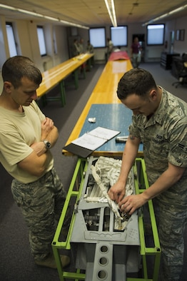 U.S. Air Force Lt. Col. Joshua Kubacz, left, 52nd Operations Support Squadron commander, learns how to pack an ejection chair parachute from Airman 1st Class Austin Lebrun, right, 52nd OSS aircrew flight equipment technician, during the commander's parachute shop familiarization tour at Spangdahlem Air Base, Germany, June 23, 2017. The aircrew flight equipment shop inspects and maintains survival gear for aircrew such as parachutes, chemical protective clothing, survival suits, helmets, and life rafts. (U.S. Air Force photo by Senior Airman Preston Cherry)