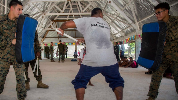 U.S. Marines with Task Force Koa Moana 17 hold striking pads for a member of the Kiribati National Police Maritime Unit while conducting striking drills on Betio Island, Tarawa Atoll, Kiribati, June 13, 2017. Koa Moana 17 is designed to improve theater security, law enforcement, and infantry training in the Pacific region in order to enhance interoperability with partner nations. (U.S. Marine Corps photo by MCIPAC Combat Camera Lance Cpl. Juan C. Bustos)