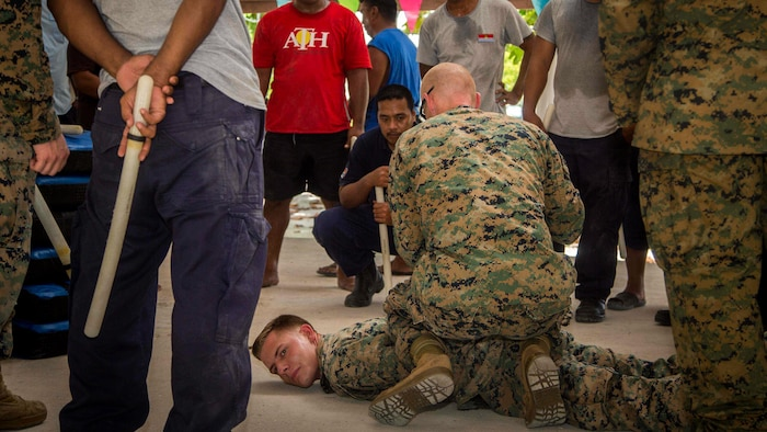 U.S. Marines with Task Force Koa Moana 17 show Kiribati residents hostile detainee handling techniques on Betio Island, Tarawa Atoll, Kiribati, June 13, 2017.  Koa Moana 17 is designed to improve theater security, law enforcement, and infantry training in the Pacific region in order to enhance interoperability with partner nations. (U.S. Marine Corps photo by MCIPAC Combat Camera Lance Cpl. Juan C. Bustos)