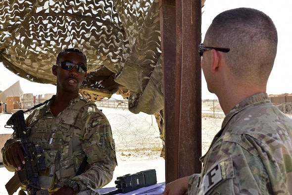 Senior Airman Sionte Campbell, 443d Expeditionary Security Forces Squadron entry controller, speaks to Capt. Jeffrey Robertson, 407th ESFS operations offficer June 22, 2017, at Al Asad Airbase, Iraq. Robertson visited security forces members at Al Asad to check on his Airmen forward deployed there and the current status and capabilities of the unit to accomplish the mission. (U.S. Air Force photo by Senior Airman Ramon A. Adelan)