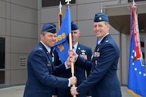 Col. Toby Doran, 50th Operations Group commander, hands the 50th Operations Support Squadron's guidon to the squadron's new commander, Lt. Col. David Gallagher, during the unit's change of command ceremony Monday, June 26, 2017 at Schriever Air Force Base, Colorado.  Gallagher was preceded by Lt. Col. Timothy Purcell.  (U.S. Air Force Photo/Dennis Rogers)