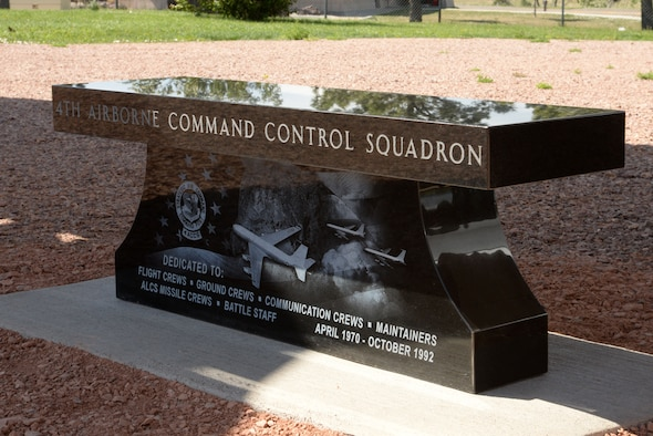 The 4th Airborne Command Control Squadron memorial bench sits on the grounds at the South Dakota Air and Space Museum, Box Elder, S.D., June 24, 2017. The memorial includes an American flag flying in the background with an image of an EC-135 aircraft flying over Mount Rushmore at the center; an image of two EC-135s conducting in-flight refueling to the right; and the squadron patch on the left. (U.S. Air Force photo by Staff Sgt. Hailey Staker)