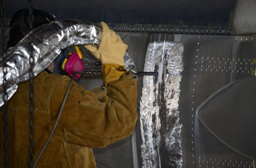 Dustin Blosmo, the chief engineer with VRC Metal Systems, repairs the side of a Martin Marietta HGM-25A Titan I with a mobile Cold Spray machine in Dock 43 at Ellsworth Air Force Base, S.D., June 22, 2017. With this technology, maintainers are able to repair thinner metals that traditional welding would not be able to do, allowing them to restore previously unrepairable objects. (U.S. Air Force photo by Airman 1st Class Donald C. Knechtel)