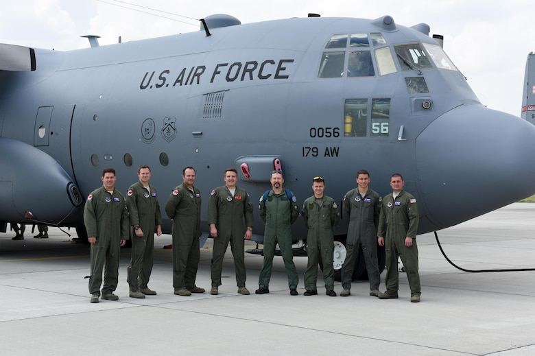 Aircrew members assigned to the Ohio Air National Guard's 179th Airlift Wing stand with two Hungarian Air Force Pilots after an orientation flight on a C-130 Hercules during Exercise Load Diffuser, in Kecskemet, Hungary, on June 6. The Ohio National Guard has a two-decade long partnership with Hungary through the National Guard's State Partnership Program, and orientation flights are another way to build relationships and enhance training with our allied nation, Hungary.