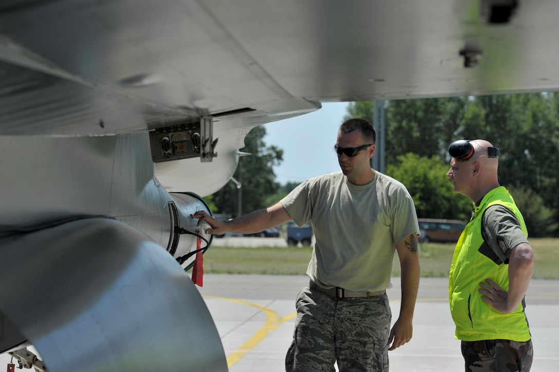U.S. Air Force Senior Airman Brad Asbury, an F-16 Fighting Falcon mechanic assigned to the 180th Fighter Wing, Ohio Air National Guard, explains preflight inspection procedures to Hungarian Air Force Maj. Oszvald Juhasz, a logistical specialist assigned to the 59th Air Base, May 30, 2017, in Kecskemet, Hungary. More than 150 Airmen from the 180FW and eight F-16s are participating in the Hungarian led, two week multinational exercise focused on enhancing interoperability capabilities and skills among NATO allied and European partner air forces by conducting joint operations and air defenses to maintain joint readiness, while also bolstering relationships within the U.S. Air National Guard's State Partnership Program initiatives. Ohio became state partners with Hungary in 1993. Air National Guard photo by Senior Master Sgt. Beth Holliker.