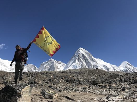 Senior Airman Sukh Bhandari, an aerospace ground equipment journeyman of the 509th Maintenance Squadron, stands with the squadron's deployment flag at Mount Everest South Base Camp May 20, 2017.  This base camp is located at an altitude of approximately 17,500 feet in Nepal. Along with Bhandari, Airman 1st Class Anish Chauhan and Senior Airman Shane Hoag, both water and fuel systems management journeymen of the 509th Civil Engineer Squadron, made the hike as well. (courtesy photo)