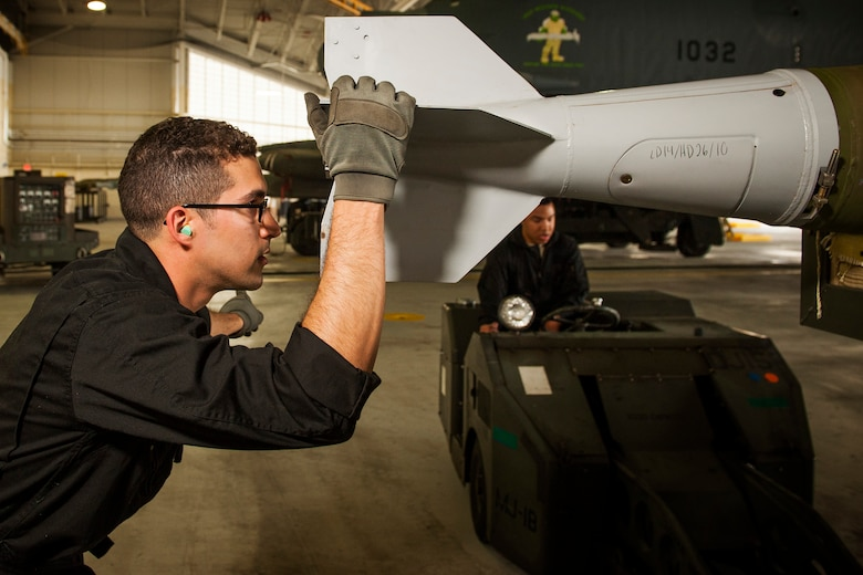 Staff Sgt. Alex Jimenez, 5th Aircraft Maintenance Squadron weapons load crew member, holds an inert GBU-38 munition at Minot Air Force Base, N.D., June 19, 2017. The muntions were inspected, loaded onto a jammer, then secured into an aircraft by the 5th AMXS Global Strike Challenge team during their bomb-loading competition. (U.S. Air Force photo/Senior Airman J.T. Armstrong)