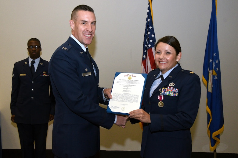 U.S. Air Force Maj. Shelby Henry, 17th Logistics Readiness Squadron Commander, receives the meritorious service medal certificate from Col. Jason Beck, 17th Mission Support Group Commander, at the Event Center on Goodfellow Air Force Base, Texas, June 27, 2017. 17th LRS welcomed their incoming commander, Maj. Curtis Shwarz, and thanked Maj. Shelby Henry, 17th LRS Commander, for her dedication and hard work. (U.S. Air Force photo by Airman 1st Class Randall Moose/Released)