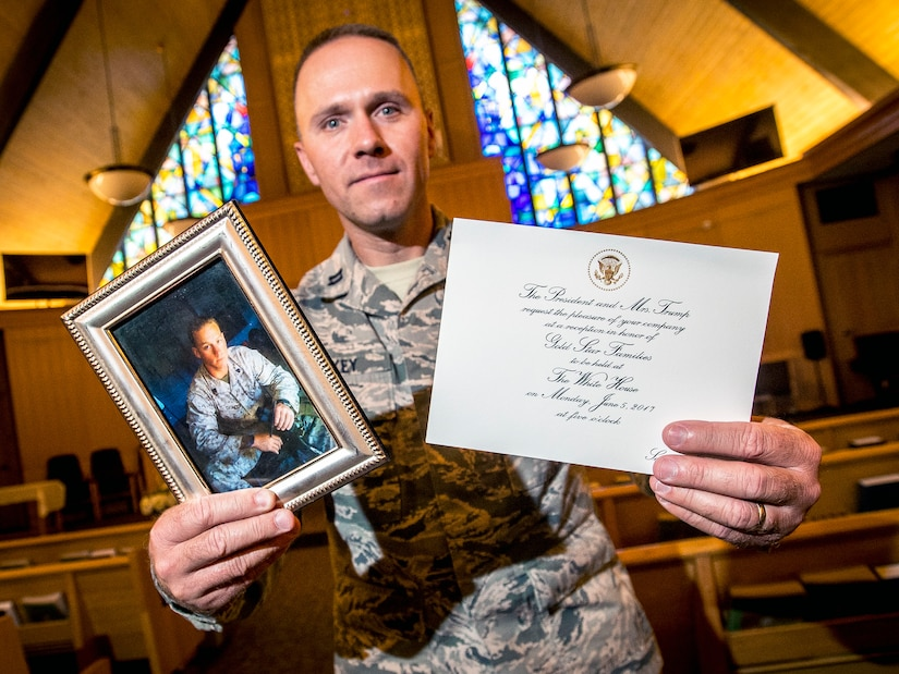 Chaplain (Capt.) Jeremy Caskey, 75th Air Base Wing, poses in the Hill Air Force Base Chapel June 22 with a photograph of his late brother, Marine Corps Sgt. Joseph Caskey, and an invitation to a reception in the White House. Chaplain Caskey visited Washington D.C. June 5 where he met President Donald Trump and First Lady Melania Trump during a reception for Gold Star families. (U.S. Air Force/Paul Holcomb)