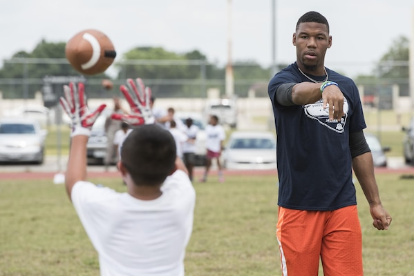 Terrance Williams, Dallas Cowboys wide receiver, throws a pass to a child during a youth football camp June 26, 2017, at Joint Base San Antonio-Randolph. JBSA-Randolph was one of 11 military communities selected to host a 2017 ProCamps football event. (U.S. Air Force photo by Senior Airman Stormy Archer)