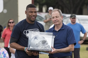 Shawn Tyson receives an autographed football helmet from Terrance Williams, Dallas Cowboys wide receiver, on behalf of the Joint Base San Antonio-Randolph Commissary June 26, 2017, at Joint Base San Antonio-Randolph. JBSA-Randolph was one of 11 military communities selected to host a 2017 ProCamps football event based on the purchase of select items at the JBSA-Randolph commissary. (U.S. Air Force photo by Senior Airman Stormy Archer)