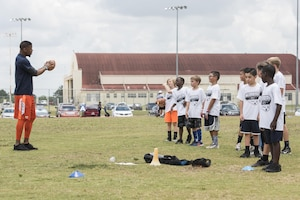 Terrance Williams, Dallas Cowboys wide receiver, coaches children during a youth football camp June 26, 2017, at Joint Base San Antonio-Randolph. JBSA-Randolph was one of the 11 military communities selected to host a 2017 ProCamps football event. (U.S. Air Force photo by Senior Airman Stormy Archer)