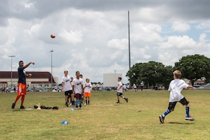 Terrance Williams, Dallas Cowboys wide receiver, throws a pass to a child during a youth football camp June 26, 2017, at Joint Base San Antonio-Randolph. JBSA-Randolph was one of the 11 military communities selected to host a 2017 ProCamps football event. (U.S. Air Force photo by Senior Airman Stormy Archer)