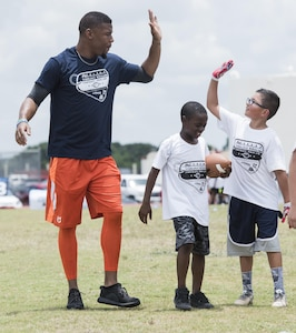 Terrance Williams, Dallas Cowboys wide receiver, high-fives a child during a youth football camp June 26, 2017, at Joint Base San Antonio-Randolph. 2017 is the fifth year the National Football League Military ProCamps program has hosted youth football camps at military installations around the world. (U.S. Air Force photo by Senior Airman Stormy Archer)