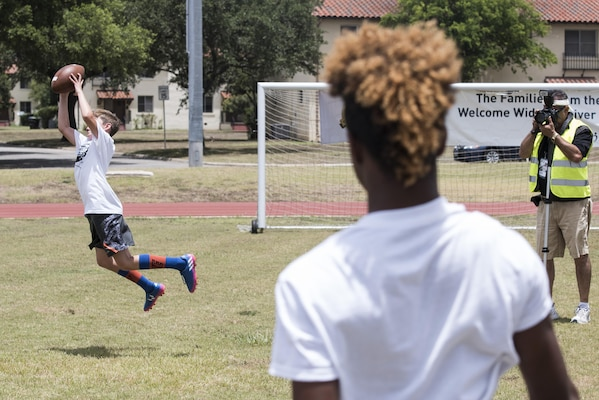 Children practice passing and catching drills during a youth football camp June 26, 2017, at Joint Base San Antonio-Randolph. This year's camp was the second camp hosted by Terrance Williams, Dallas Cowboys wide receiver, at JBSA-Randolph in three years. (U.S. Air Force photo by Senior Airman Stormy Archer)