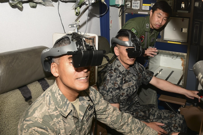U.S. Air Force Chief Master Sgt. Terrence Greene, the fifth Air Force command chief, and Warrant Officer Katsumi Yamazaki, the senior enlisted advisor of the Japan Air Self Defense Force (JASDF), look through JASDF KC-767 goggles, June 23, 2017, at Eielson Air Force Base, Alaska. The JASDF KC-767 boom operators control the boom from a seat behind the cockpit. (U.S. Air Force photo by Airman 1st Class Isaac Johnson)