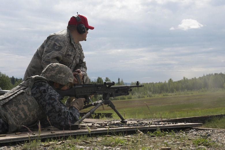 Warrant Office Katsumi Yamakazi, the Japan Air Self Defense Force (JASDF) senior enlisted advisor, fires an M240 machine gun with guidance from U.S. Air Force Tech. Sgt. Tommy Nelson, the 354th Security Forces Squadron non-commissioned officer in charge of combat arms, June 23, 2017, at Eielson Air Force Base, Alaska. Yamazaki will soon retire after serving in the JASDF for more than 34 years. (U.S. Air Force photo by Airman 1st Class Isaac Johnson)