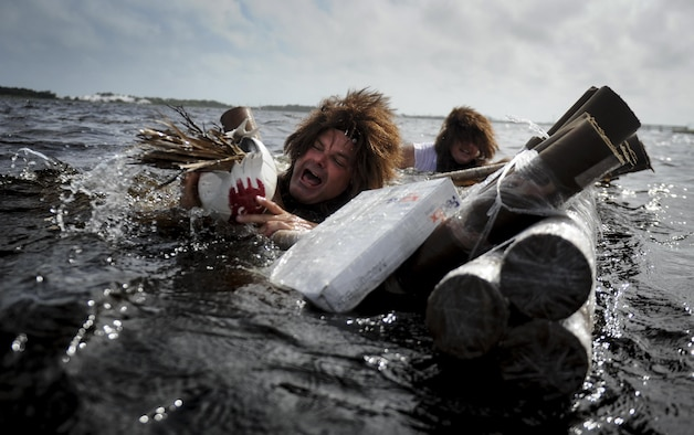 """Mike Raynor, left, and Stuart Camp, public affairs specialists with Air Force Special Operations Command Public Affairs, sink during the cardboard boat regatta at Hurlburt Field, Fla., June 24, 2017. Raynor and Camp dressed up as actor Tom Hanks' character from the famous movie """"Cast Away."""" (U.S. Air Force photo by Airman 1st Class Dennis Spain)"""
