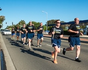 """Members of the 60th Security Forces Squadron run with """"The Flame of Hope"""" Special Olympics Torch at Travis Air Force Base, Calif., June 22, 2017. The defenders are running the torch to the California Department of Corrections prison facility in Vacaville, Calif. The event brings local law enforcement together from Solano County to show their support for the Special Olympics. (U.S. Air Force photo by Louis Briscese)"""
