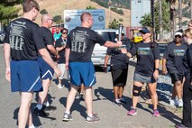 """Members of the 60th Security Forces Squadron deliver """"The Flame of Hope"""" Special Olympics Torch to the California Department of Corrections prison facility in Vacaville, Calif., June 22, 2017. The defenders joined local law enforcement from Solano County to show their support for the Special Olympics. (U.S. Air Force photo by Louis Briscese)"""